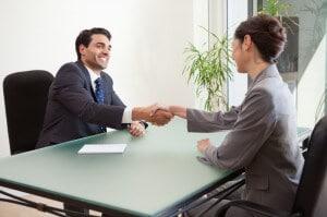 business-handshake-at-desk-300x199